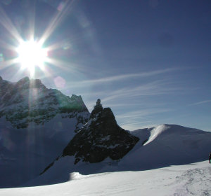 The sun over the Jungfrau mountain in early evening with the Sphinx laboratory visible in the foreground