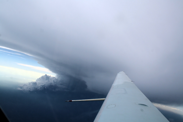 A huge anvil outflow just above the Egrett. The convective system producing the anvil can also be seen just below the wing of the aircraft.