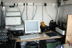 The laser, and optical bench (right hand side of image), along with heater controller, computer, digital signal processor, photodetecor module, and rotator controller (stack at left of image). Deployment in the Tow-A-Van mobile lab during the NAMBLEX project, August 2002.